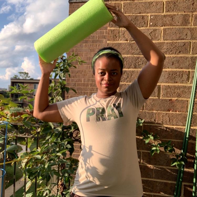 Michelle holding a green foam roller overhead
